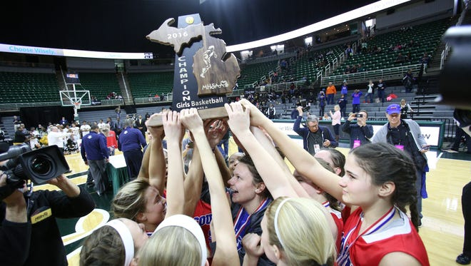 Warren Cousino holds up the trophy after defeating Detroit King, 67-65, during the Class A final at the Breslin Center on March 19, 2016.