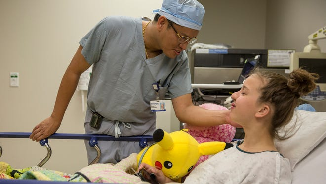 Dr. Kongkrit Chaiyasate, center, greets Charlotte Ponce, 14, of Spring Lake, before explaining the surgery to her and her family, Thursday, June 15, 2017 at Beaumont Hospital in Royal Oak.
