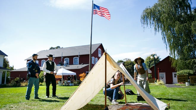 (Left to right) Andrew Engel and Jeff Meek watch as Michelle Bruhn and Serianna Rosberg work together to pitch a tent at the Fort Laramie station at the Oregon Trail Live event on Saturday, Sept. 9, 2017, at the Willamette Heritage Center. Engel and Meek are on the Northwest Civil War Council, and volunteered as characters for the event.