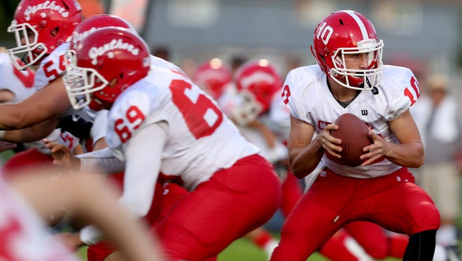 Central's Peter Mendazona (10) looks to hand off the ball in the Central vs. Dallas football game at Dallas High School on Friday, Sept. 29, 2017.