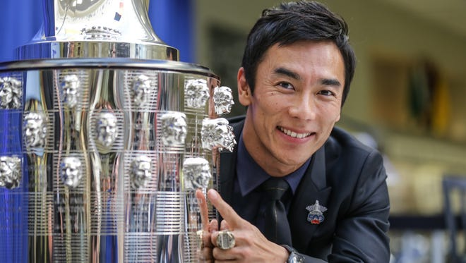 IndyCar driver and 2017 Indy 500 winner Takuma Sato points to his likeness on theBorg-Warner Trophy during a event held at the Indianapolis Motor Speedway Museum on Tuesday, Oct. 17, 2017.