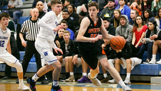 Silverton's Cade Roth (15) drives toward the basket in a game against Woodburn on Tuesday, Feb. 13, 2018, at Woodburn High School.