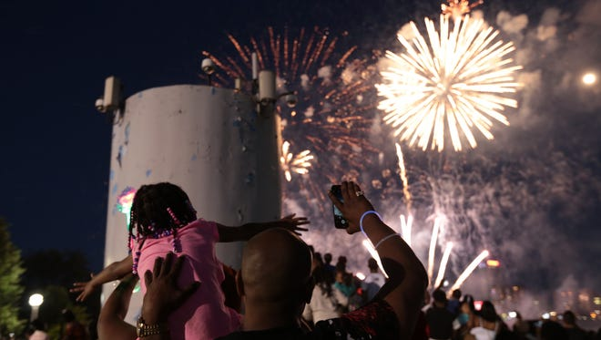 People react as they watch fireworks go off above the Detroit River during the 2018 Ford Fireworks at Hart Plaza in downtown Detroit on Monday, June 25, 2018.