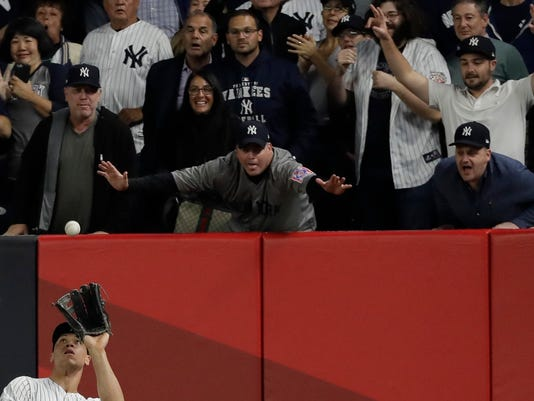 Fans watch as New York Yankees' Aaron Judge catches a long fly ball hit by Houston Astros' Alex Bregman during the seventh inning of Game 5 of baseball's American League Championship Series Wednesday, Oct. 18, 2017, in New York. (AP Photo/David J. Phillip)