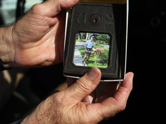 Tim Kelly holds a photo of himself delivering the mail