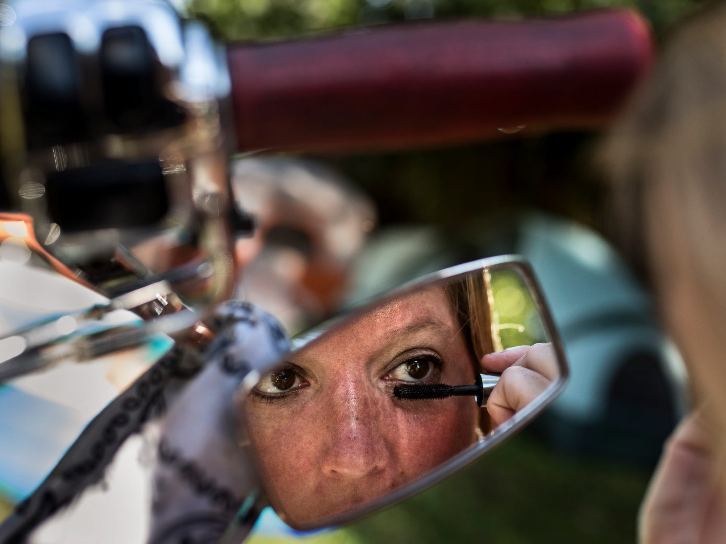 Felecia Blevins puts her makeup on in a motorcycle