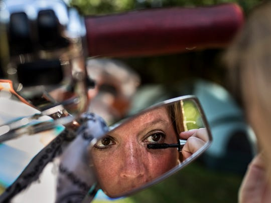 Felecia Blevins puts her makeup on in a motorcycle mirror Friday before heading to the Miss Sturgis pageant and the evening festivities at the Sturgis Kentucky Bike Rally. July 14, 2017