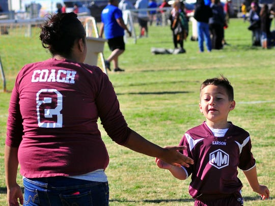 "Derek Kulpa, 7, gets a ""five"" from his Mighty Minions team coach Amy Gardea as he runs off the field Saturday, April 16, at Provencio Van Dam soccer fields in Las Cruces."