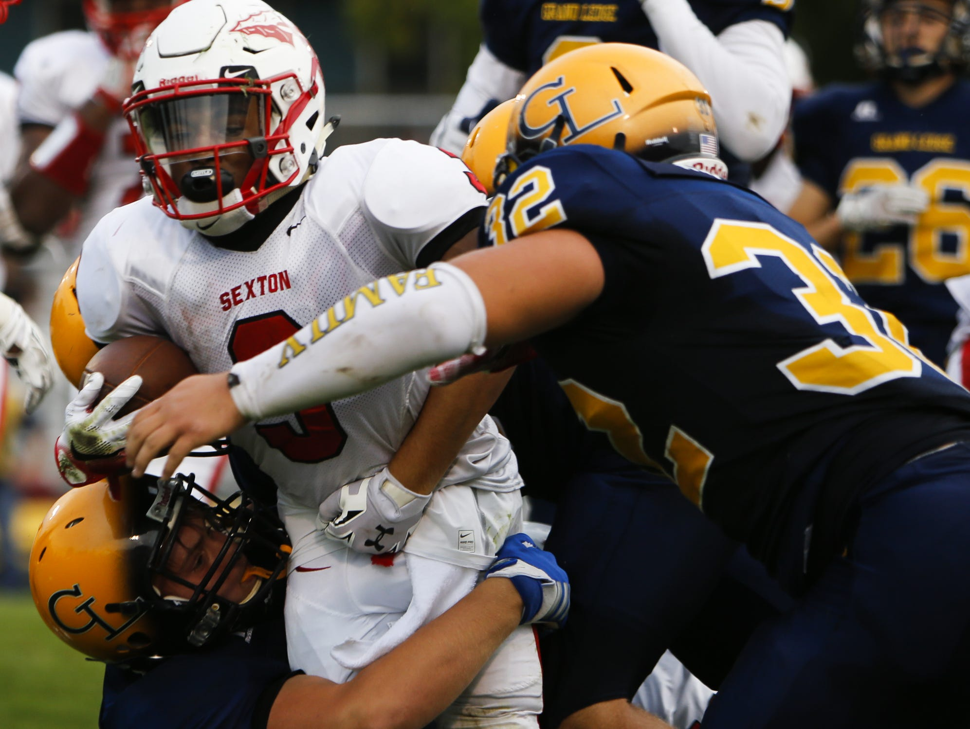 Cody Blankenburg, shown carrying the ball against Grand Ledge last week, is evolving into a playmaker for Sexton. The junior had four touchdowns in the Big Reds' 41-28 win over Jackson on Friday, which included returning an interception for a score.