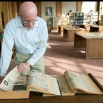 Barry Cowan, assistant archivist for the University Archives at LSU's Hill Memorial Library, browses old issues of The Daily Reveille, LSU's student newspaper, in Hill Memorial Library's reading room. The files are deteriorting and Hill Library is launching a program to restore and digitize the historic issues.