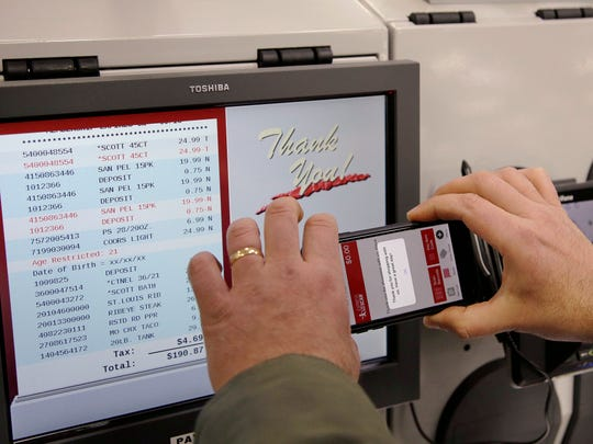 Tony D'Angelo uses the BJ's Express Scan app on his cell phone to check out after completing his shopping at the BJ's Wholesale Club in Northborough, Mass. More stores are letting customer tally their choices with a phone app or store device as they roam the aisles.