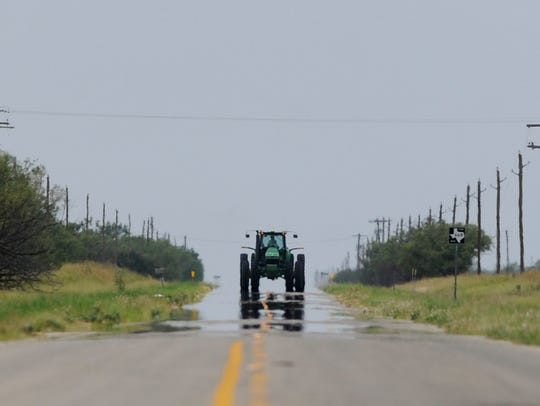 A tractor is reflected in the heat coming off FM 668