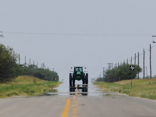 A tractor is reflected in the heat coming off FM 668 in Jones County July 31, 2017.