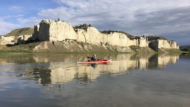 Buck Nelson paddles past white cliffs on the Missouri River as he traces the Lewis and Clark Trail from east to west.