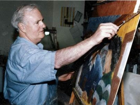 Tom Seigenthaler paints in his home art studio, which