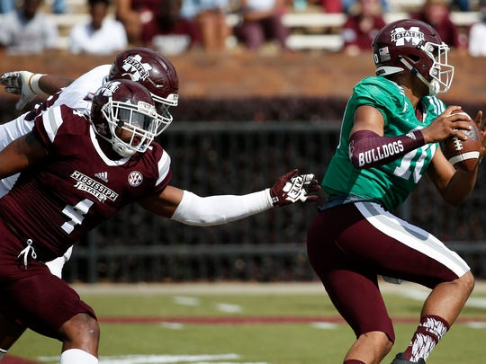 Although there was to be no contact on the quarterbacks, Maroon linebacker Gerri Green (4) manages to get a hand on White quarterback Keytaon Thompson (10) as he set up to pass during the first half of Mississippi State's Maroon and White spring NCAA college football game, Saturday, April 21, 2018, in Starkville, Miss. (AP Photo/Rogelio V. Solis)