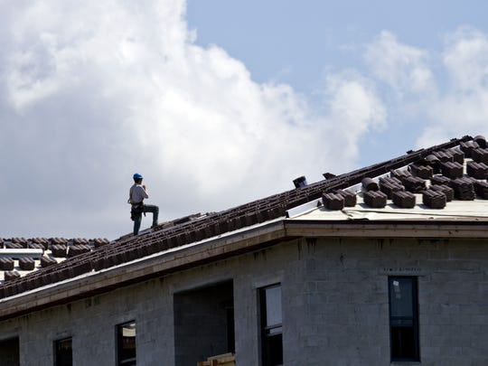A worker at the site of the new apartment complex Channelside prepares roofing materials in south Fort Myers last month.