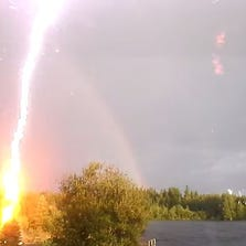 Lightning strikes while woman records a rainbow