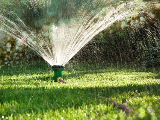 Close-up of a lawn sprinkler watering a lawn