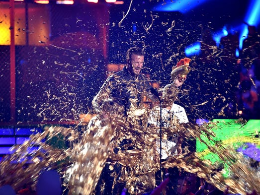 Cruz David Beckham, former soccer player David Beckham and Romeo James Beckham get slimed onstage during Nickelodeon Kids' Choice Sports Awards 2014 at UCLA's Pauley Pavilion on July 17, 2014, in Los Angeles.