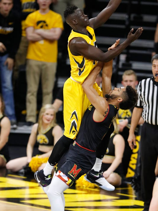 Iowa guard Peter Jok is fouled by Maryland guard Melo Trimble, right, while driving to the basket during the first half of an NCAA college basketball game, Thursday, Jan. 19, 2017, in Iowa City, Iowa. (AP Photo/Charlie Neibergall)