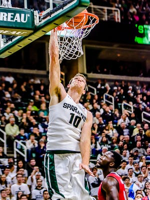 Matt Costello ,10, of MSU dunks over C.J. Turman of Florida Atlantic after an assist by teammate Denzel Valentine in the 2nd half of their season opener Friday.  Costello added a team high 15 points to the Spartan effort.
