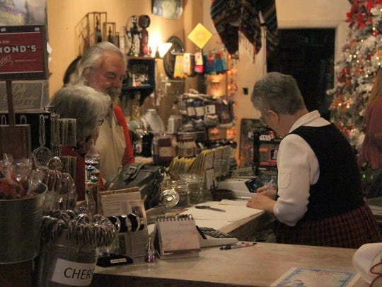 Victoria owner Miss Alice takes a customer's order at her specialty shop during Small Business. Saturday