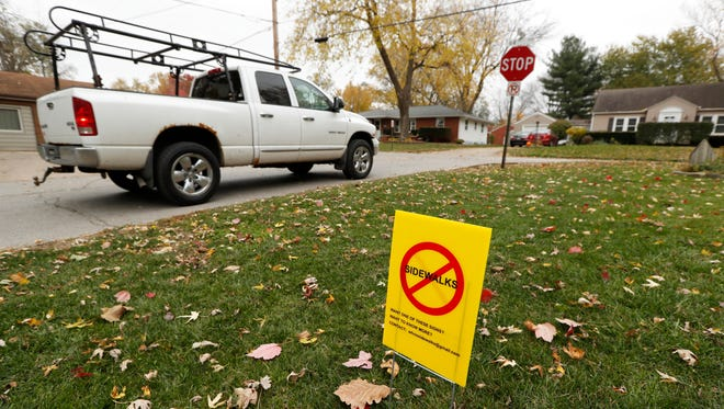 A truck passes a sidewalks protest sign in a front yard, Monday, Oct. 31, 2016, in Windsor Heights, Iowa. When officials in the Des Moines suburb of Windsor Heights began talking about installing sidewalks to improve safety and encourage outdoor activities, they anticipated some grumbling from residents who liked the look of uninterrupted, lush lawns. They didn't expect packed City Council meetings, protest signs stretching down leafy suburban streets and threats to defeat officials in the next election. (AP Photo/Charlie Neibergall)