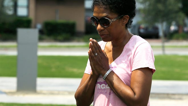 Laura Manns-Huggins prays outside a makeshift memorial, Monday, June 13, 2016, for the victims of a fatal shooting at Pulse. A gunman opened fire in a crowded Orlando nightclub early Sunday killing dozens of people.