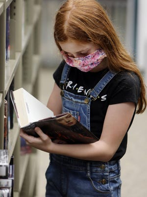 Emma Hutchinson, 11, picks out books on the first day the Burlington Public Library reopened to the public after closing its doors due to the coronavirus pandemic.
