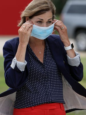 Iowa Governor Kim Reynolds puts on a face mask as she arrives to visit the Test Iowa Clinic Site June 23 on the Southeastern Community College campus in West Burlington.