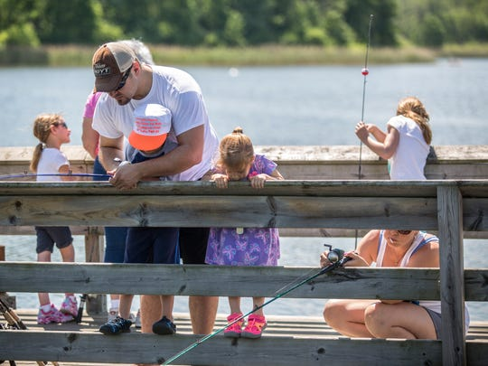 Bob and Kendra Hordiyenko, of Armada, fish with their children Alexander, 4, and Olivia, 2, during a free fishing clinic Saturday, June 11, 2016 at the 40th Street pond in Port Huron Township.