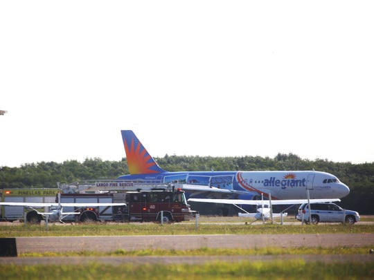 An Allegiant Airbus jet lands safely at St. Petersburg Clearwater International Airport, Thursday morning after the pilot report problems.  Emergency vehicles wait nearby next to the north south runway.