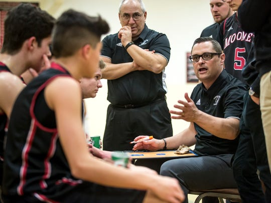 Cardinal Mooney coach Mike McAndrews talks with players on the bench during the Cardinal Mooney Christmas Basketball Tournament Wednesday, Dec. 28, 2016 at Cardinal Mooney High School in Marine City.