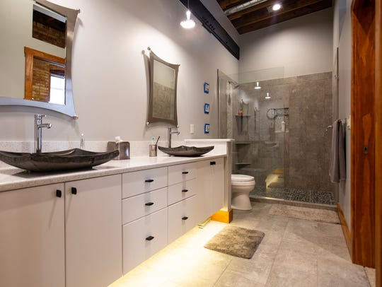 The floating vanity and open glass shower serves as