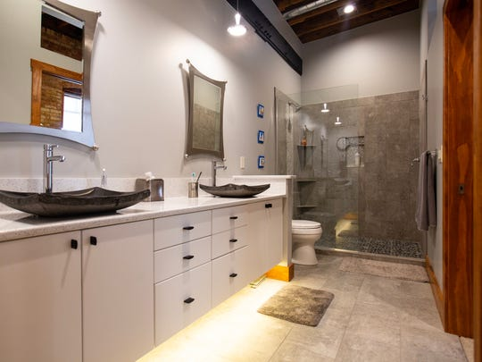 The floating vanity and open glass shower serves as a modern touch inside the industrial-inspired home.