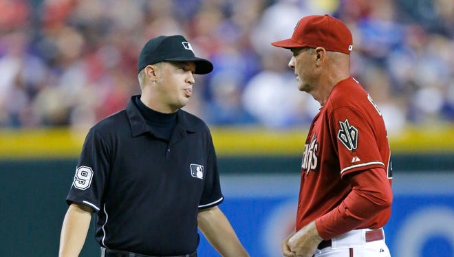 Arizona Diamondbacks manager Kirk Gibson (23) argues with   Umpire Cory Blaser  after Mark Trumbo (15) slid into second in the 7th inning of their 3-2 win over the Chicago Cubs in their MLB game Sunday, July 20, 2014 in Phoenix, Ariz.  Following replay Trumbo was ruled safe at second.