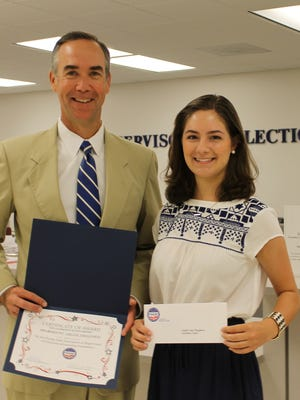 Supervisor of Elections David H. Stafford presenting Abigail Megginson with the Joe Oldmixon Florida State Association of Supervisors of Elections (FSASE) scholarship.