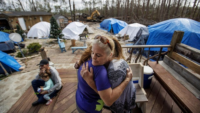 "Diahnn ""Shelly"" Summers, right, embraces Lori Hogan, who is currently living in a tent in Summers' backyard months after Hurricane Michael hit in Youngstown, Fla."