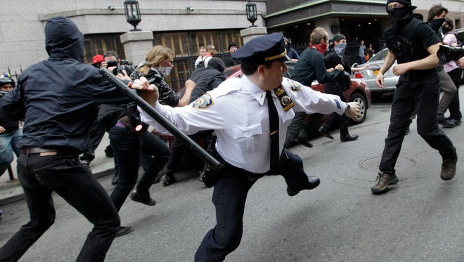 A police lieutenant swings his baton at Occupy Wall Street activists in New York on May 1, 2012. This photo is among the many put on Twitter in response to a New York Police Department request for Twitter users to share pictures of themselves posing with police officers.