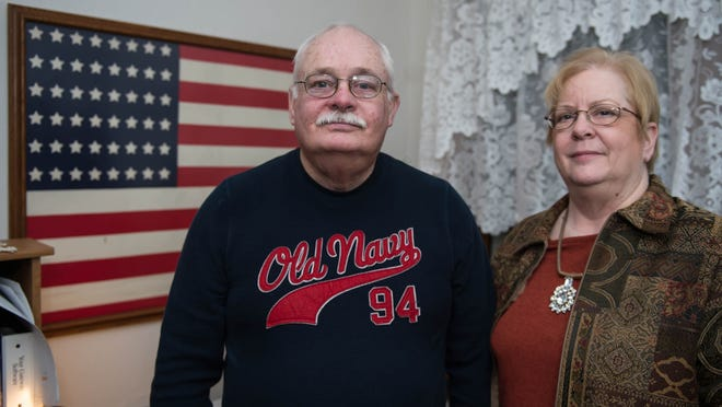 Gary Head and Cindy Cheyne stand in front of a U.S. flag that was saved by their dad, Floyd Head, from the USS Quincy in 1942.