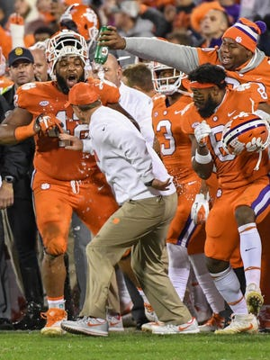 Clemson defensive tackle Christian Wilkins (42), left, linebacker Dorian O'Daniel (6), and defensive lineman Dexter Lawrence (90) douse head coach Dabo Swinney with water after the team beat Florida State 31-14 in Memorial Stadium at Clemson on Saturday.