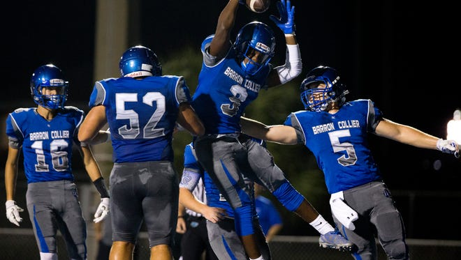 Barron Collier's Michael McClay (3) celebrates with teammates after scoring the first touchdown of the game during the first quarter of action against Dixie Hollins at Barron Collier High School Friday, August 19, 2016 in Naples. Barron Collier led 14-0 at the end of the first.