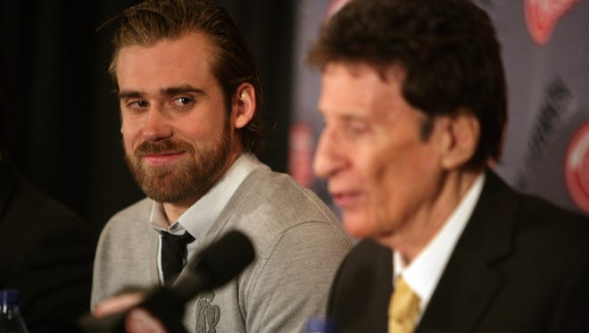 Henrik Zetterberg, left, listens to owner Mike Ilitch during a press conference announcing Zetterberg's contract in 2008.