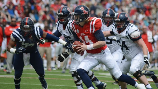 Ole Miss quarterback Bo Wallace scrambles during Saturday's Grove Bowl in Oxford, as center Ben Still (64) and others block.
