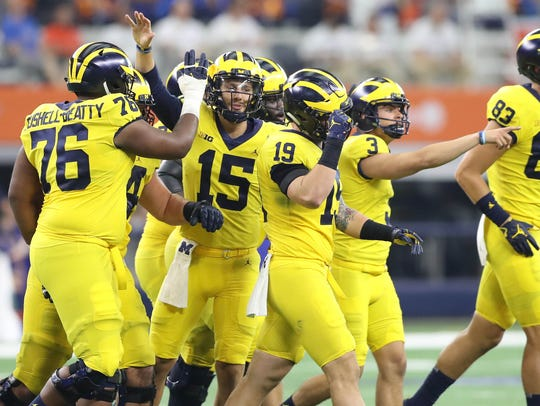 Michigan's Garrett Moores (15) celebrates after a field