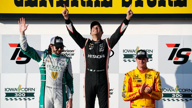 Helio Castroneves, center, of Brazil, celebrates in Victory Lane with second-place finisher JR Hildebrand, left, and third-place finisher Ryan Hunter-Reay, right, after winning a IndyCar Series auto race Sunday, July 9, 2017, at Iowa Speedway in Newton, Iowa. (AP Photo/Charlie Neibergall)