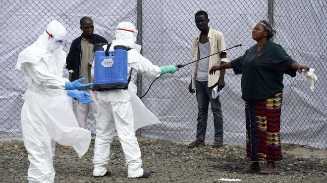 Medical personnel at the Ebola treatment center at Island hospital in Monrovia disinfect people who brought patients suspected of having the Ebola virus on Oct. 2.