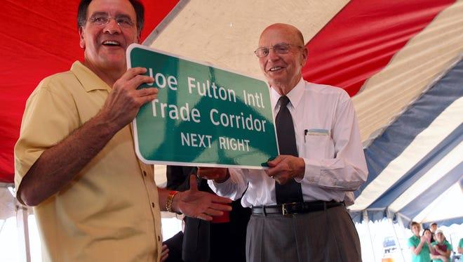 Port of Corpus Christi Chairman Ruben Bonilla (left) presents Joe Fulton (right) with a highway roadsign during the ceremonies celebrating the opening of the Joe Fulton International Trade Corridor on Oct. 19, 2007.