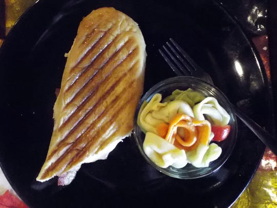 "A ""Turkey Tantrum"" panini with a pasta salad on the side."
